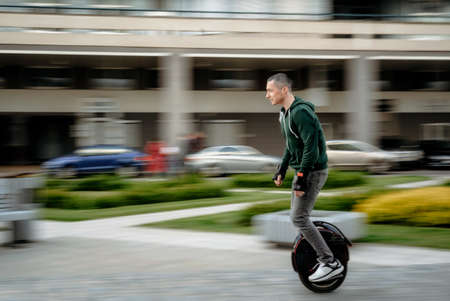 Man riding unicycle on street, electric unicycle, motion blur Reklamní fotografie