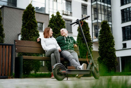 Couple sit next to electric kick scooter in street and laughing.