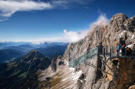 Tourists stand on observation deck of skywalk rope bridge Dachstein Mountains and enjoys the landscape in Austria Redakční
