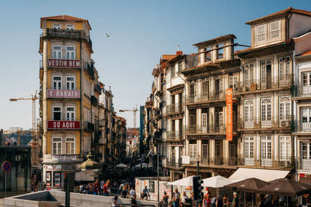 Porto, Portugal - September 27, 2018: Traditional Portuguese house, with windows and ornate metal balcony railings. Old building wall with glazed ceramic tiles.