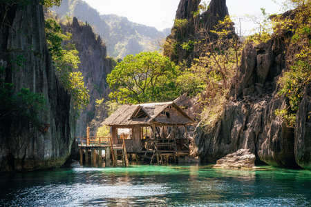 View of wooden hut In calm sea against rock formation, Philippines