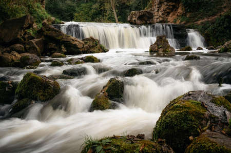 Motion blur waterfall among trees, green leaves, rocks and stones in forest with cascade river in Belarus.