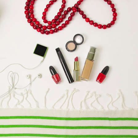 preparation of a woman for the holiday in red and green colors - on the table a tone cream, lipstick, mascara, lip gloss, beige shadows, red nail polish. flatlay. filming on top. green shoes. white and green fabric, striped fabric Stock Photo