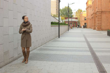 Young woman in a beige coat stands near a brick wall, does not look at the camera Stock Photo