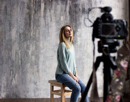backstage with professional shooting in the studio, the model sits on a chair with close eyes, a professional camera in the defocus