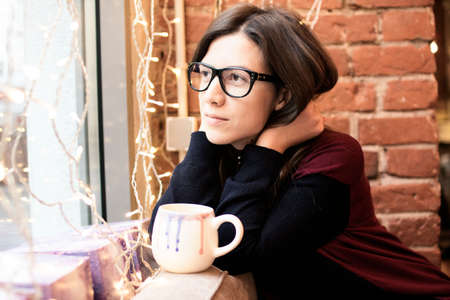 A young woman in glasses sits near a window in a cafe with a cup of coffee and looks thoughtfully out the window. on a background of a brick wall and garland