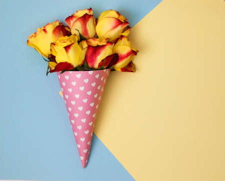 bouquets of roses in a paper horn with hearts on a blue and yellow background. a gift for St. Valentines Day. gift for International Womens Day
