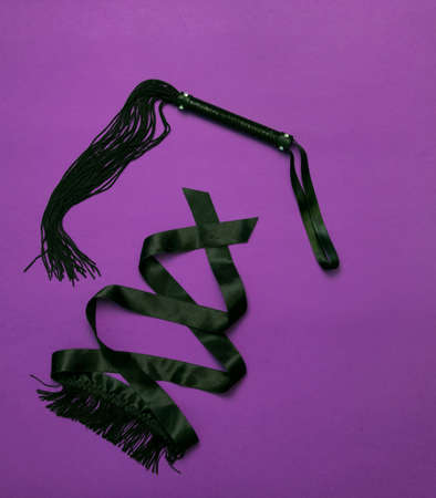 Womens things for a romantic evening - lacy black underwear, black whip, eye patch with fringe on a ultraviolet background. Valentines Day. Love and passion Stock Photo