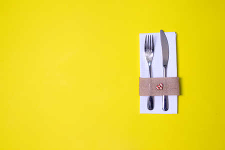 white napkin, knife and fork, place for dinner served in rustic style on a yellow background.