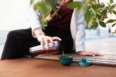 Traveler girl pouring tea in cup  , outdoors. Young woman drinking tea at . Theme travel. Woman pouring a hot drink in mug. gaiwan