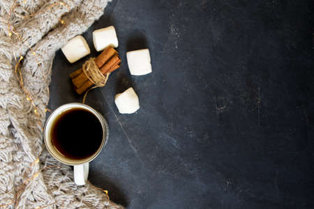 Winter composition. Cup of coffee, cookie, lights on a dark background. Flat lay
