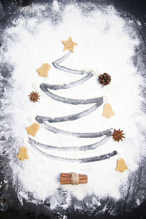 Christmas cooking: fir tree made from flour on a dark table, ingredients for baking and dried fruits on dark background