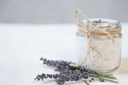 Natural herbal sea salt with aromatic lavender - perfect for relaxation. Cosmetic jars and bottles with salt, lavender flowers