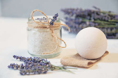 Natural herbal sea salt with aromatic lavender - perfect for relaxation. Cosmetic jars and bottles with salt, lavender flowers, bath bomb