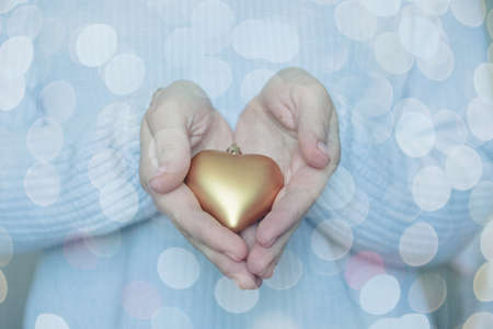 Woman hands are holding a beautiful glossy gold heart in a snow winter background. Love and St. Valentine cozy concept. 스톡 콘텐츠