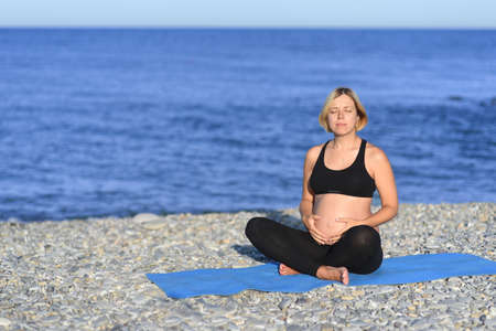 A portrait of a pregnant asian woman doing yoga in the sea shore