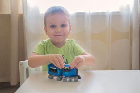 boy play with constructor train made with colored bricks close up portrait