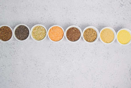 Collection of different groats on grey background. Top view of buckwheat, chia, flax, amaranth, lentils, couscous, wheat