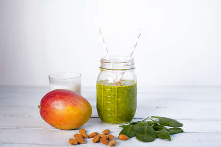 Components of healthy Green Reach Vitamins Smoothie with baby leaf spinach, mango, almond milk and strawberry