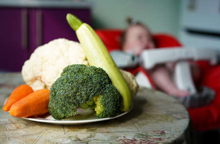 a plate of vegetables - broccoli, zucchini, carrots and cauliflower. Little baby on the background