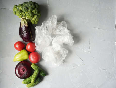 different vegetables lie in a row next to the plastic bags in which they were packed. zero waste concept