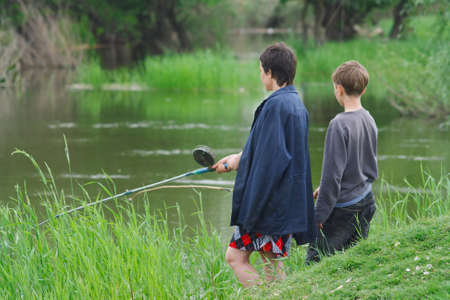 Mother and son catch the fish on the river shore Stock Photo