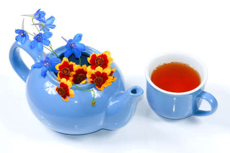 The blue kettle with nice flowers and cup of tea photo