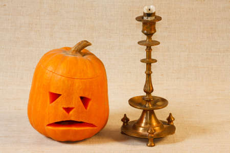 The sad halloween pumpkin with candle from canvas background photo