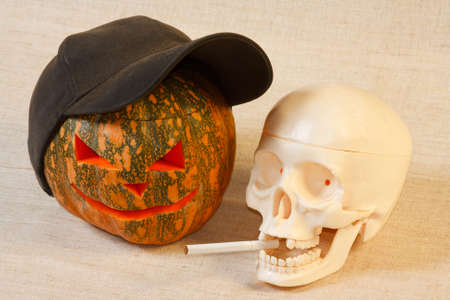 The cheerful halloween pumpkin and skull with cigarette from canvas background Stock Photo - 9906709