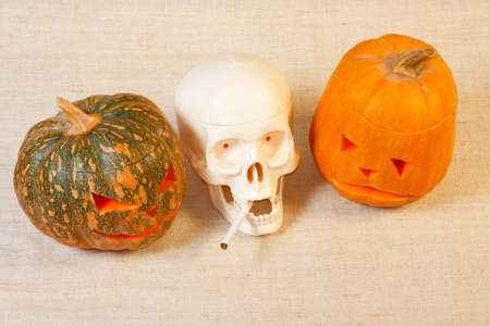 The cheerful and sad halloween pumpkin and skull with cigarette from canvas background photo