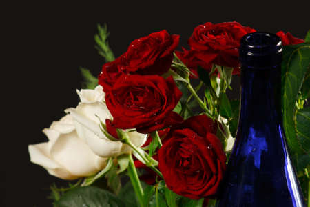 The bouquet red and creamy roses and blue bottle neck from dark background photo