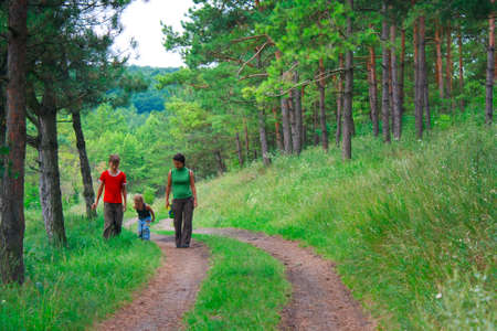Family in the green woods for a walk