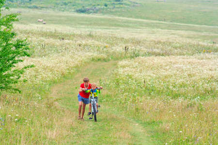 Two brothers are walking on a bike outdoors photo