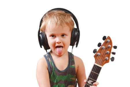 Little boy with headphones and guitar on white background photo