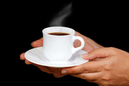 Hands with a cup of coffee with steam on a black background