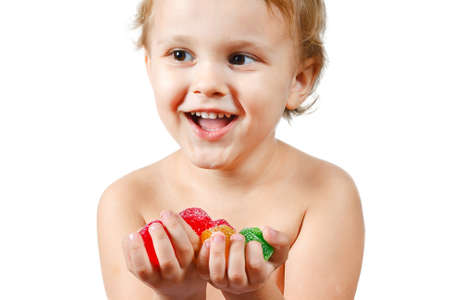 Little boy with colored jelly candies on white background photo
