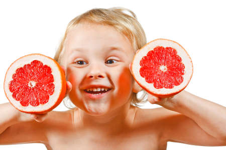 Little boy with a pink grapefruit on a white background photo