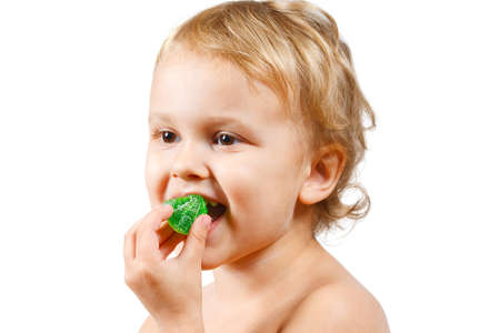 Little boy with green jelly candy on white background photo