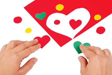 Hands combine red and green hearts on a white background photo
