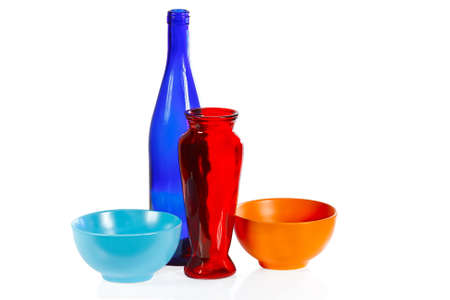 Coloured ceramic cups, glass bottle and vase on a white background photo