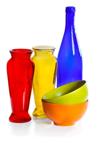 Coloured ceramic cups, glass bottle and vases on a white background photo