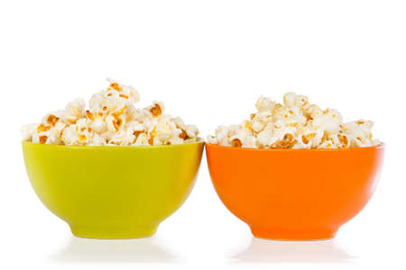 Popcorn in orange and green bowl on a white background Stock Photo