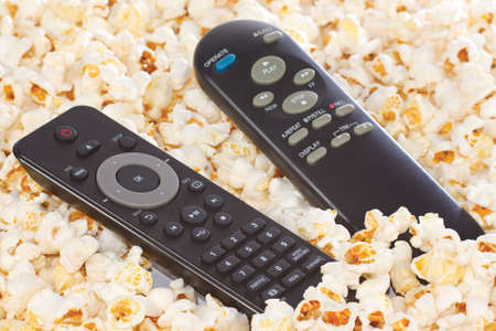 remote controls: Remote controls of players in popcorn closeup Stock Photo