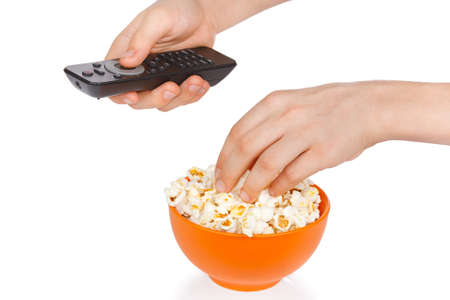 Hands a teenager with popcorn and remote control on a white background photo