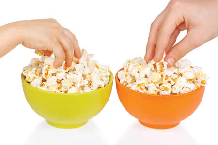 Hands of children eating popcorn on a white background photo
