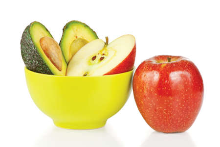 Sliced fresh apples and avocado in ceramic cup on a white background photo