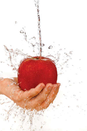 Red apple in hand under flowing water on a white background photo