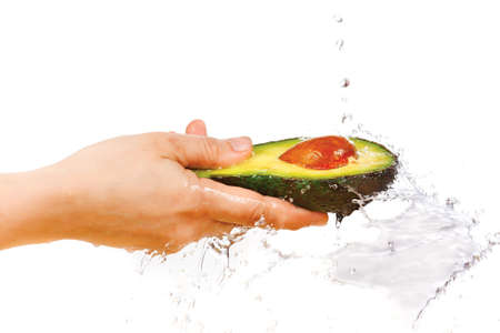 Fresh avocado in hand under flowing water on a white background