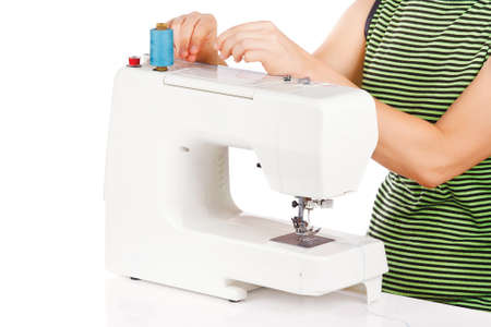 Woman is sewing on the sewing machine on a white background photo