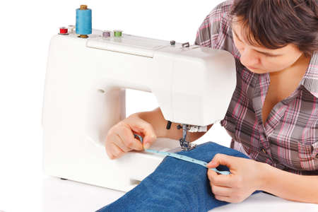 making dresses: Woman is sewing on the sewing machine on a white background Stock Photo